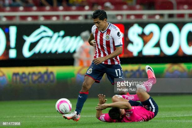 Jesus Sanchez of Chivas dribbles Carlos Gerardo Rodriguez of Morelia during the 13th round match between Chivas and Morelia as part of the Torneo...