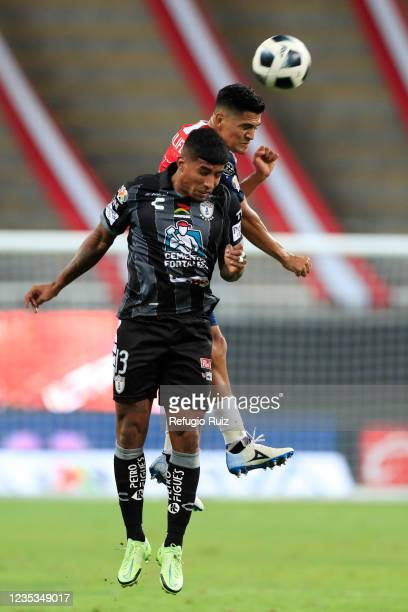 Jesus Sanchez of Chivas jumps for the ball with Kevin Oscar Murillo of Pachuca during the 9th round match between Chivas and Pachuca as part of the...