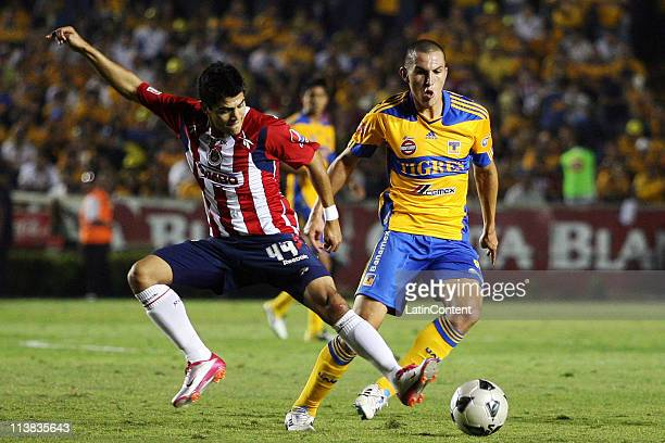 Jesus Sanchez of Chivas struggles for the ball with Danilo Veron of Tigres during a quarter finals match as part of the Clausura Tournament 2011 at...