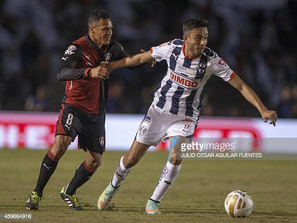 Jesus Savala of Monterrey and Aldo Leao of Atlas vie for the ball during their quarterfinal football match of the 2014 Mexican Apertura tournament...