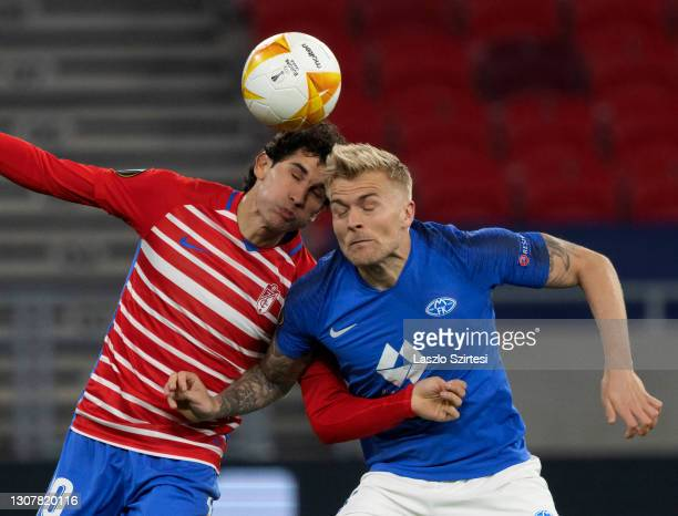 Jesus Vallejo of Granada CF battles for the ball in the air with Eirik Ulland Andersen of FK Molde during the UEFA Europa League Round of 16 Second...