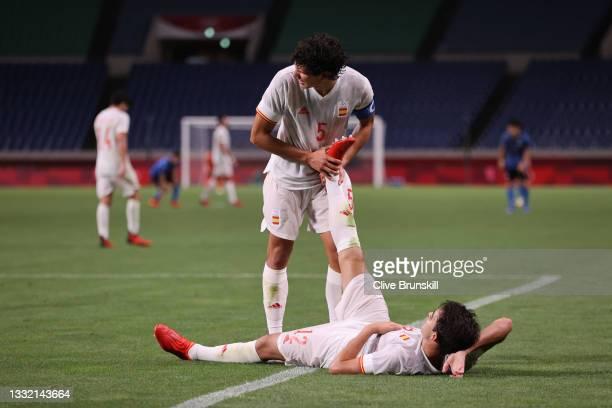 Jesus Vallejo of Team Spain helps teammate Eric Garcia of Team Spain after victory in the Men's Football Semi-final match between Japan and Spain on...
