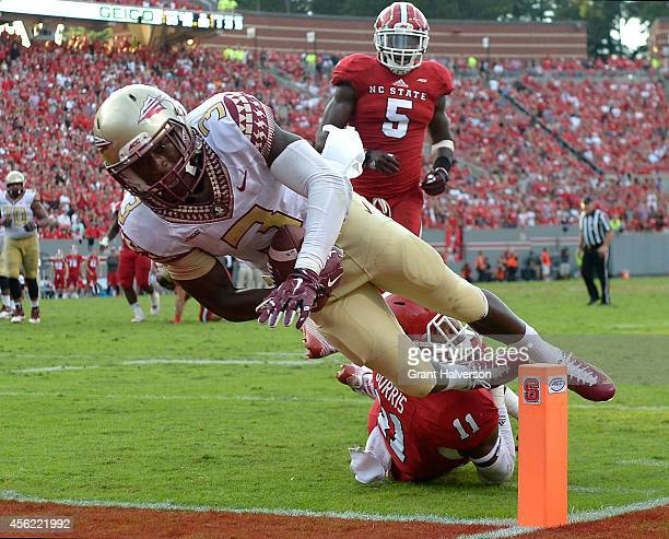 Jesus Wilson of the Florida State Seminoles dives over Juston Burris of the North Carolina State Wolfpack for a tochdown during their game at...