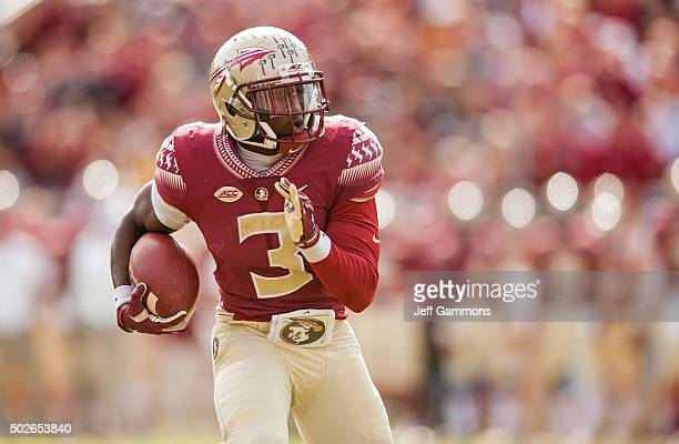 Jesus Wilson of the Florida State Seminoles tries to find a gap in the North Carolina State Wolfpack defense during the game at Doak Campbell Stadium...