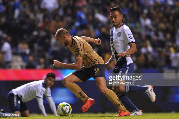 Jesus Zavala of Puebla vies for the ball with Carlos Gonzalez of Pumas during their Mexican Clausura 2019 tournament football match at Cuauhtemoc...