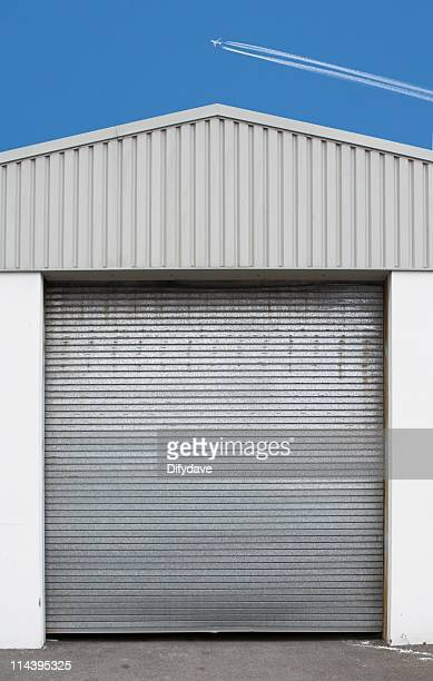 jet airliner in blue sky above factory building - roller shutter stock pictures, royalty-free photos & images
