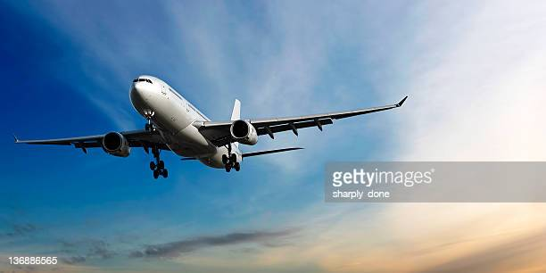 xl jet airplane landing at dusk - commercial aviation stock photos and pictures