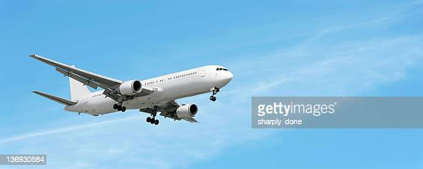 jet airplane landing in bright sky