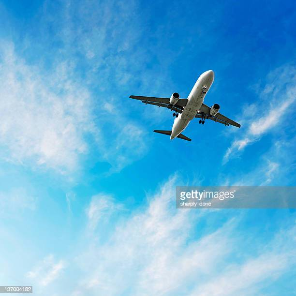 xl jet airplane landing in bright sky - aeroplane stock pictures, royalty-free photos & images