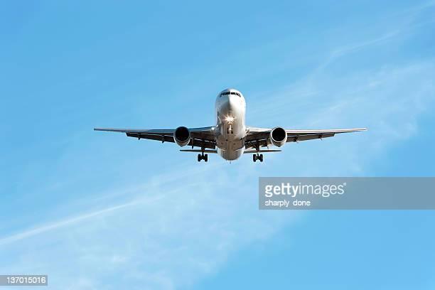 XL jet airplane landing in bright sky