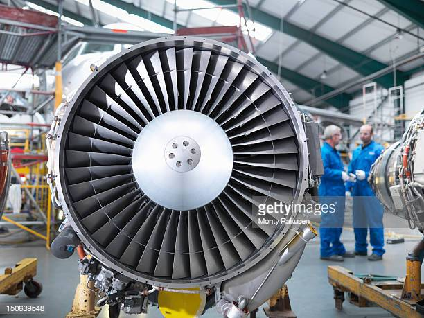 jet engines of airplane with aircraft engineers in background - jet engine stock photos and pictures