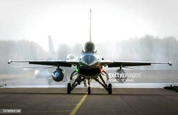 A F16 jet fighter of Royal Dutch Air Force lands on the runway of Volkel air base southern Netherlands on January 2 2019 The Dutch Air Force took...