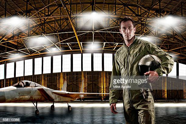 jet fighter pilot posing next to his aircraft in hangar - mike agliolo stock pictures, royalty-free photos & images