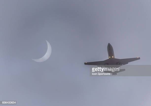 A jet flying by the eclipse on its approach to Oakland Airport through the fog in the Bay Area during the Total Solar Eclipse on August 21 2017 in...