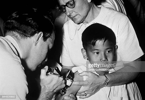 A jet injector gun being used during mass smallpox immunization procedures 1972 Vaccinia vaccine is a highly effective immunizing agent that brought...