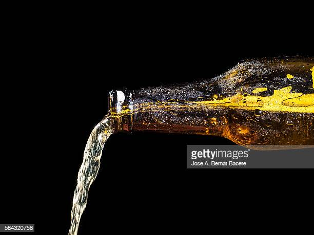 jet of a bottle of cold beer of crystal on a black bottom - fülle stock-fotos und bilder