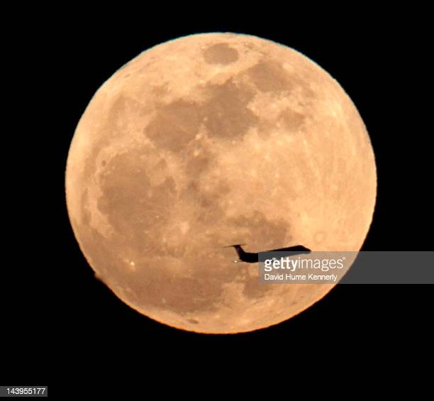 A jet on the approach to Los Angeles International Airport crosses in front of the Super Moon an event that occurs when the full moon reaches the...