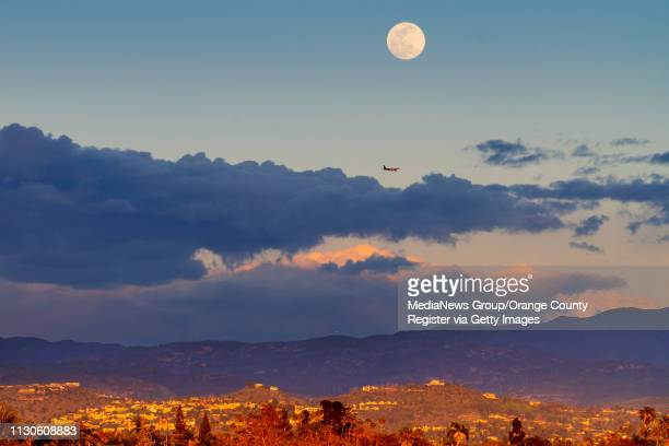 A jet passes beneath the super snow moon as it rises above the clouds at sunset as seen from Santa Ana on Monday February 18 2019 This is the second...