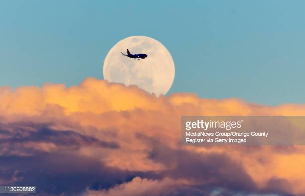 A jet passes the super snow moon as it rises above the clouds as seen from Santa Ana on Monday February 18 2019 This is the second of 2019's three...