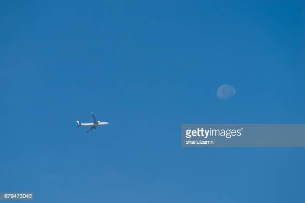 a jet plane flying past the moon over blue sky - shaifulzamri stock-fotos und bilder