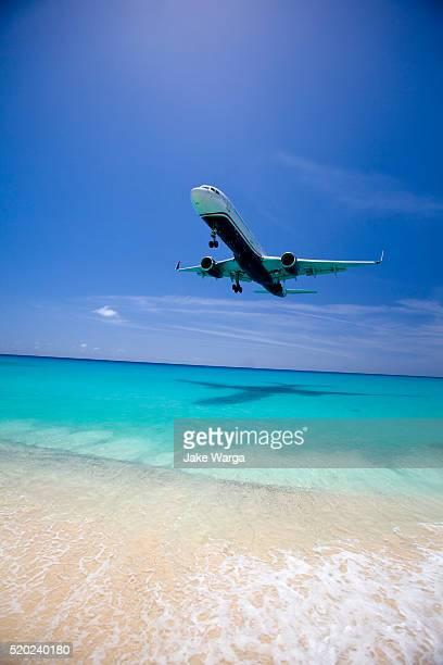 jet plane over beach during landing at st. maarten - jake warga stock pictures, royalty-free photos & images