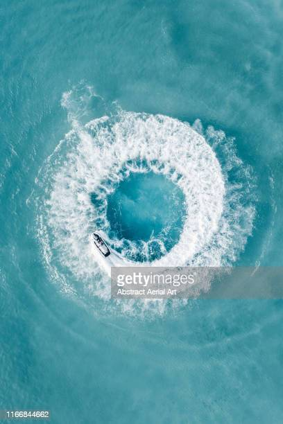 jet ski doing circles shot by drone, barbados - barbados stock pictures, royalty-free photos & images