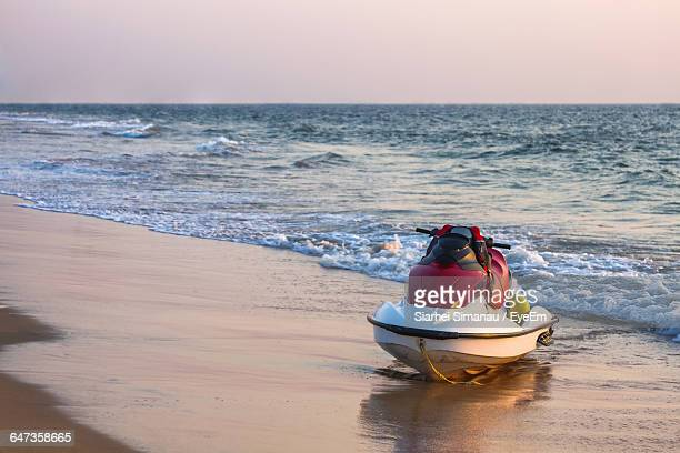 jet ski moored at beach against sky during sunset - jet ski stock pictures, royalty-free photos & images