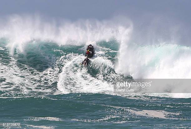 A jet ski with members of the water safety crew power over a wave during The Quiksilver in Memory of Eddie Aikau at Waimea Bay on February 25 2016 in...