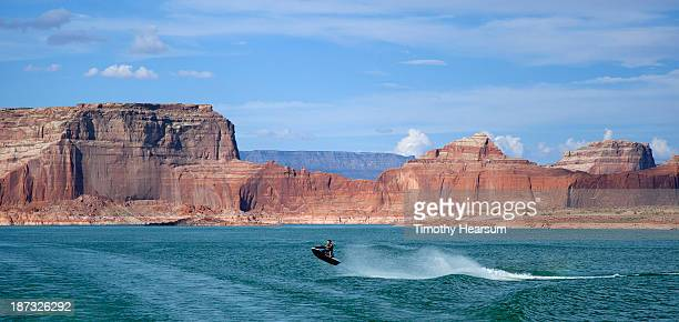 jet ski with red rock formations beyond - timothy hearsum stock pictures, royalty-free photos & images