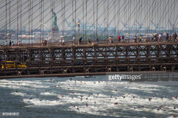 Jet skiers cross under the Brooklyn Bridge and toward the Statue of Liberty as they ride in the East River, June 9, 2018 in New York City. Hundreds...