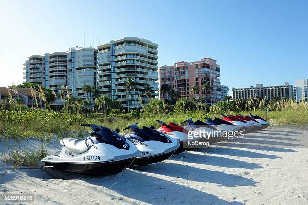 jet skis on sand in front of oceanfront buildings - marco island stock pictures, royalty-free photos & images