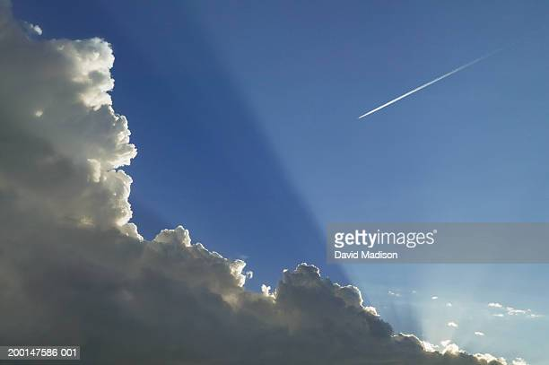 Jet vapor trail and clouds across blue sky