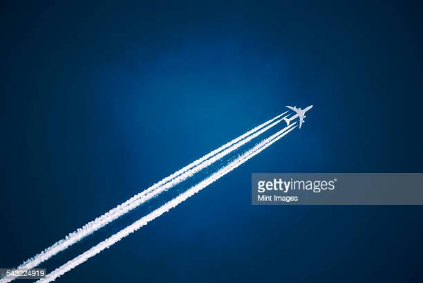 a jet vapour trail across a dark blue sky. - track imprint stock photos and pictures
