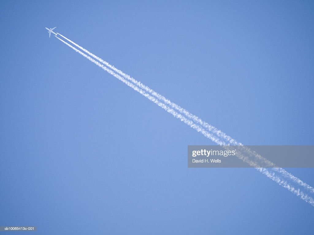 Jet with vapour tail on blue sky : Foto stock