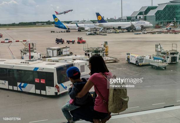 Jet2 airplane takes off while a tourist shows to her child Ukraine International and Lufthansa airplanes sitting on the tarmac at Terminal 1 of...