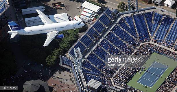 JetBlue airplane files over as Lukas Dlouhy of the Czech Republic and Leander Paes of India play against Mahesh Bhupathi of India and Mark Knowles of...