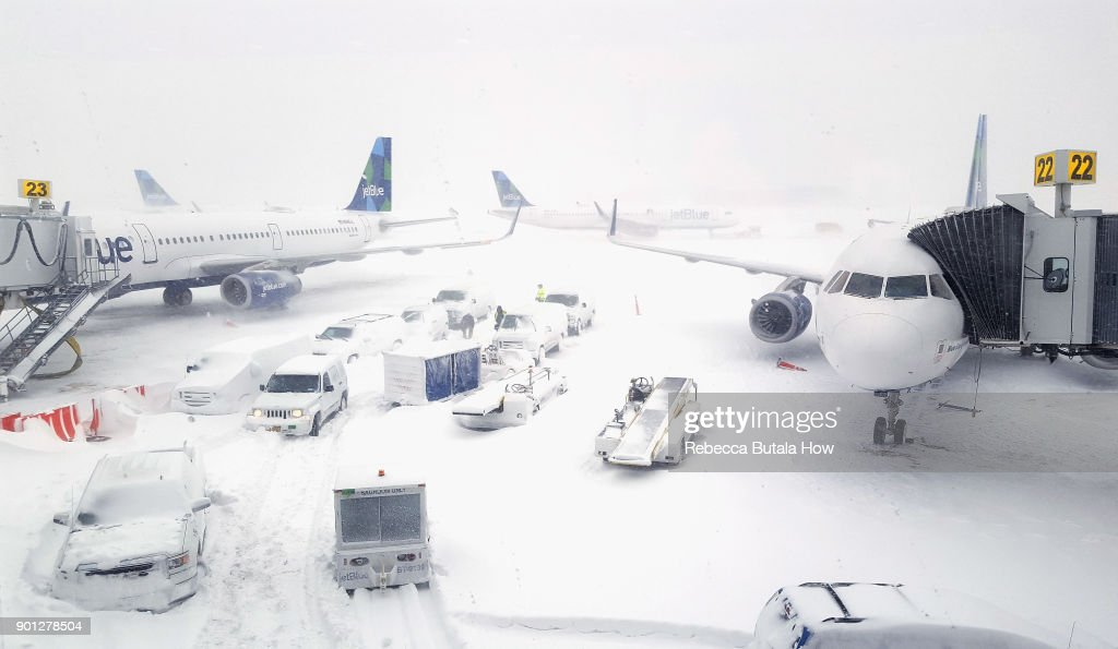 JetBlue airplanes wait at the gates outside terminal five at John F. Kennedy International Airport on January 4, 2018 in the Queens borough of New York City. A winter storm is traveling up the east coast of the United States dumping snow and creating blizzard like conditions in many areas.