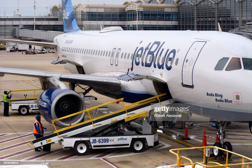 A JetBlue Airways Airbus A320 jet is serviced at a gate at