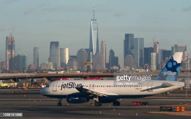 JetBlue Airways airplane passes by the skyline of lower Manhattan in New York City as it heads to a runway for takeoff at Newark Liberty Airport on...