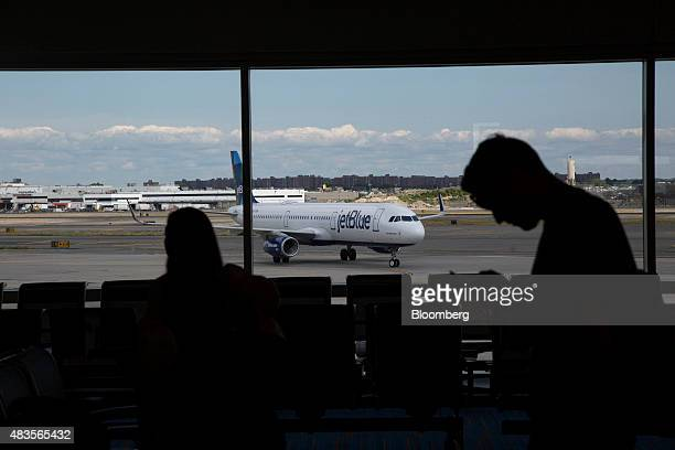 A JetBlue Airways Corp plane taxis as passengers wait in Terminal 5 at John F Kennedy International Airport airport in New York US on Friday Aug 7...