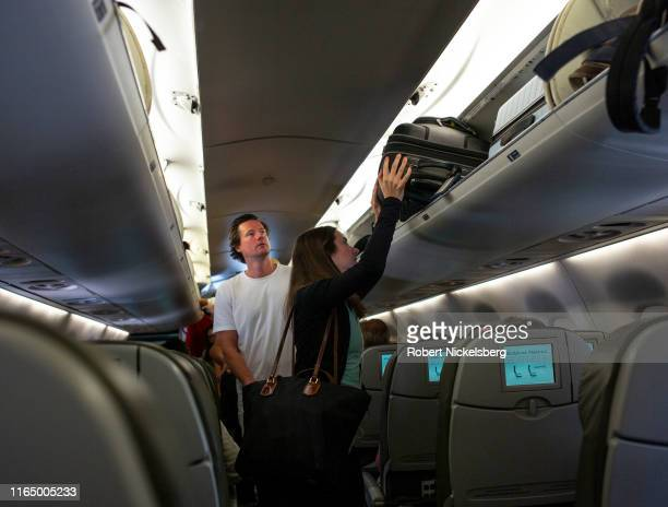 JetBlue Airways passenger places her luggage in an overhead compartment at John F Kennedy International Airport in New York City on July 25, 2019....