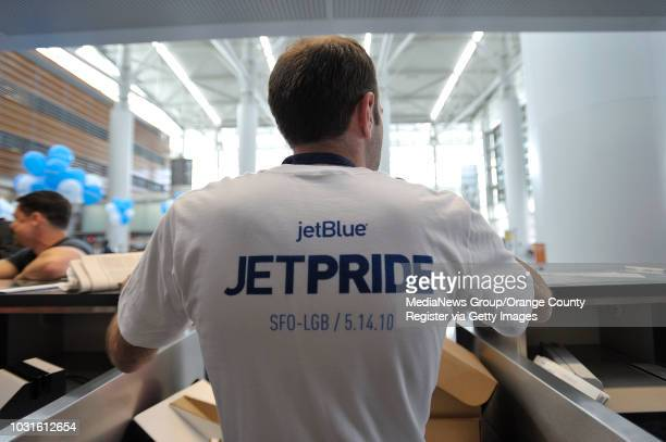 USA JetBlue Airway's Sebastiaon White dons a commemorative shirt at the ticket counter before boarding JetBlue's JetPride flight 1969 from San...