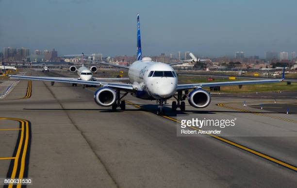 JetBlue passenger jet and other departing aircraft taxi toward the runway at LaGuardia Airport in New York New York
