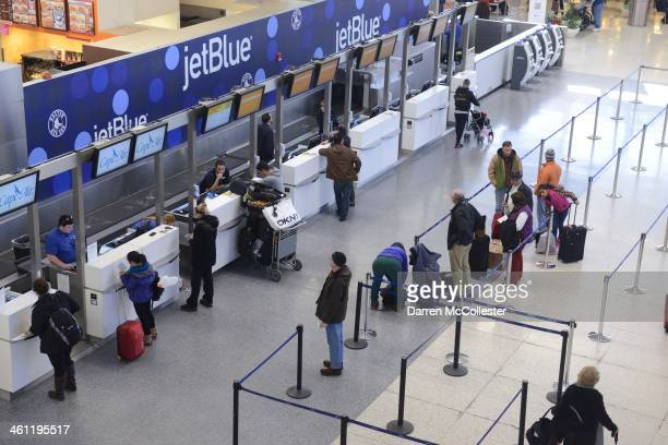 JetBlue passengers stand in thin lines while waiting for normal flights to resume later this afternoon in Terminal C at Logan International Airport...