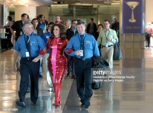 USA JetBlue pilots Michael Jorgensen left and James Daulton escort comedian and 'air hostess' Pam Ann to the gate before passengers board JetBlue's...