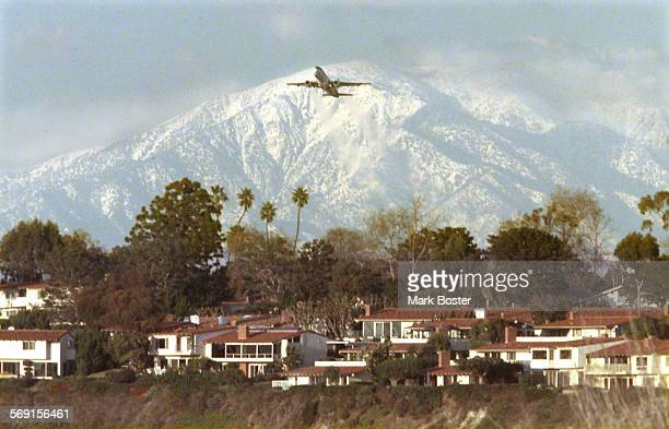 A jetliner lifting off from John Wayne Airport is dwarfed by the snow capped peaks of Mount Baldy tuesday afternoon photographed from the Upper...
