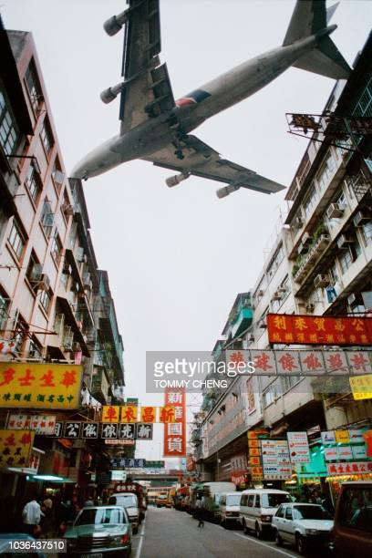 A jetliner screeches past the ageing and tatty apartment blocks of Kowloon city where aircraft landing and taking off Kai Tak international airport...