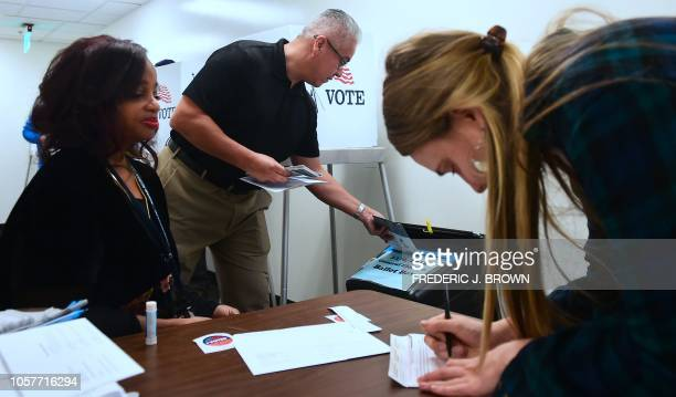 Jetoi Johnson working to help ensure ballots are signed before being submitted watches as a voter signs her ballot while another drops his off into...