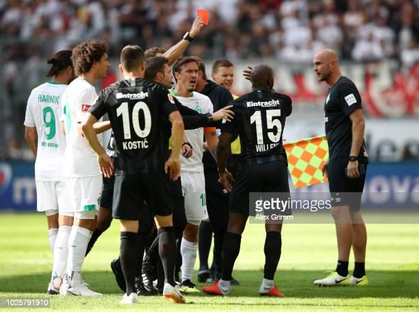 Jetro Willems of Eintracht Frankfurt is shown a red card by referee Sören Storks during the Bundesliga match between Eintracht Frankfurt and SV...