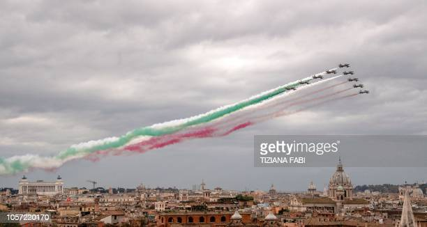 TOPSHOT Jets of the Italian Air Force aerobatic unit Frecce Tricolori spread smoke with the colors of the Italian flag as they fly over the city of...